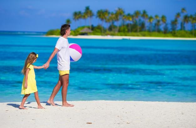 Het gelukkige vader en dochter spelen met bal openlucht op strand