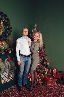 Het gelukkige verliefde paar viert nieuw jaar samen en glimlacht voor foto in kerstsfeer