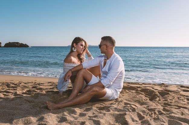 Het gelukkige verliefde paar, zit op het strand tijdens zonsondergang of zonsopgang.