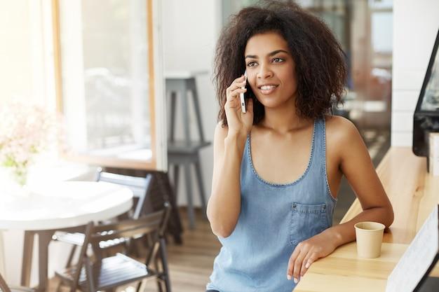 Het gelukkige vrolijke mooie afrikaanse vrouw glimlachen die op telefoonzitting spreken in koffie.