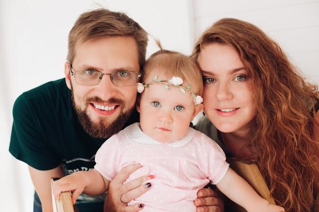 Het gelukkige vrolijke paar spelen met babymeisje thuis