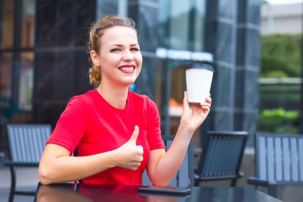 Het gelukkige vrolijke positieve meisje, jonge mooie vrouw in rode reclamekoffie om in witboekkop te gaan, toont duim, zoals gebaar, in openlucht wijd in koffie glimlachen. coffeine, energie ochtend concept