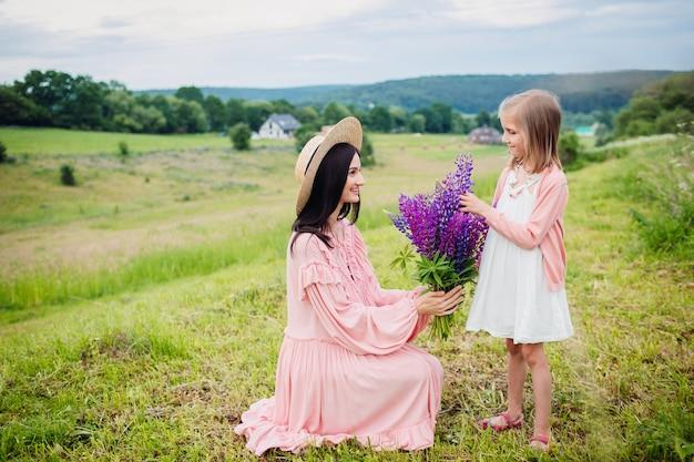 Het gelukkige vrouw en het meisje stellen met boeket van lavander op het gebied