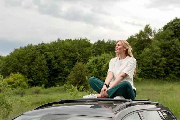 Het gelukkige vrouw stellen bovenop auto in aard