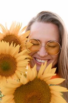 Het gelukkige vrouw stellen met zonnebloemen