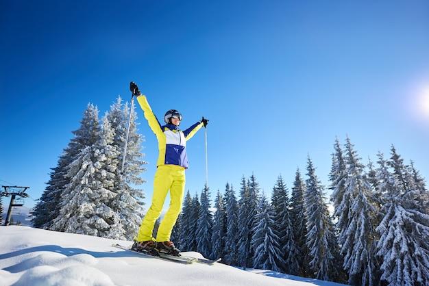 Het gelukkige vrouw stellen op ski's alvorens te skiën. zonnige dag in skigebied. heldere blauwe lucht, met sneeuw bedekte sparren op de achtergrond.
