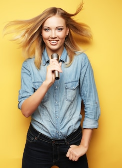 Het gelukkige vrouw zingen in gele microfoon