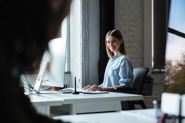 Het gelukkige vrouwenwerk in bureau dat computer met behulp van