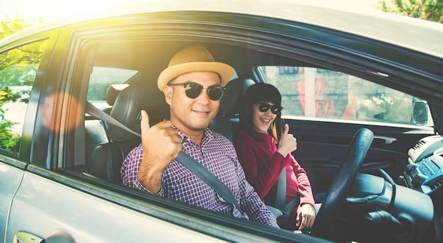 Het gelukzitting van het vooraanzicht toont het aziatische paar in auto duim.