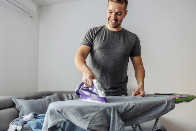 Het gemak van het strijken van wasgoed door een jonge glimlachende man