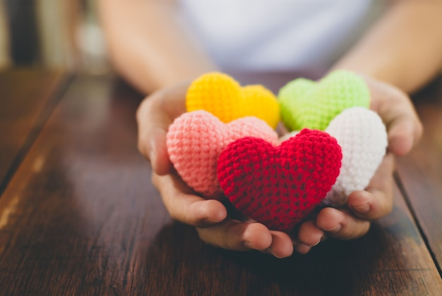 Het gemengde hart van het kleurengaren bij het geven van handen. close-up van kleurrijke handgemaakte.