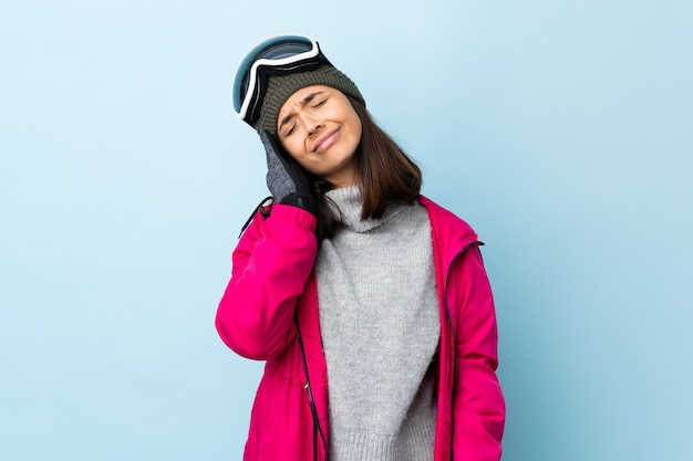 Het gemengde meisje van de rasskiër met snowboardende glazen op geïsoleerd blauw met hoofdpijn