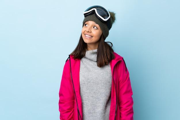 Het gemengde meisje van de rasskiër met snowboardende glazen over geïsoleerd blauw die een idee denken terwijl omhoog het kijken
