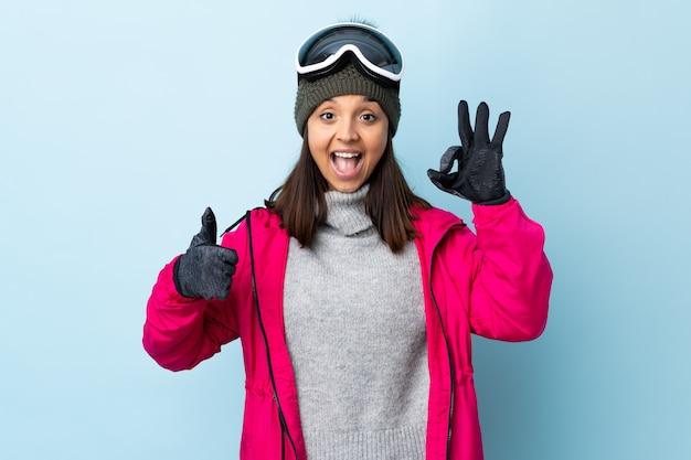 Het gemengde meisje van de rasskiër met snowboardende glazen over geïsoleerd blauw die ok teken en duim op gebaar tonen