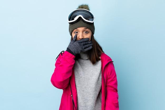 Het gemengde meisje van de rasskiër met snowboardende glazen over geïsoleerde blauwe die mond behandelen met hand