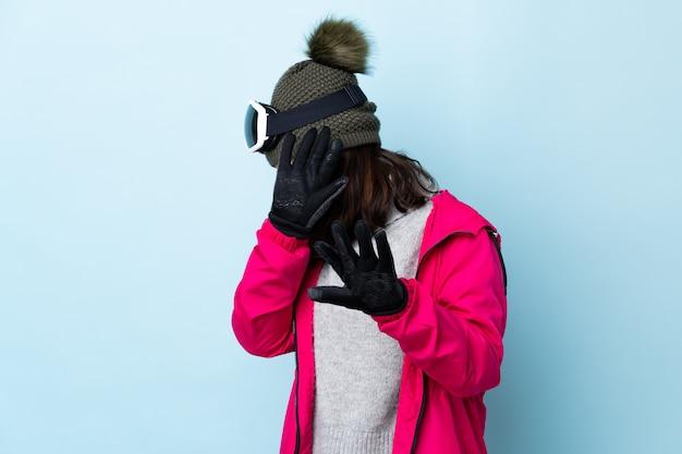 Het gemengde meisje van de rasskiër met snowboardende glazen over geïsoleerde blauwe zenuwachtige het uitrekken zich handen aan de voorzijde.