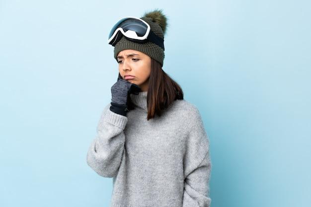 Het gemengde meisje van de rasskiër met snowboardglazen over geïsoleerd blauw die twijfels hebben.