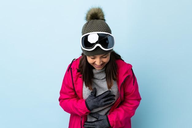 Het gemengde meisje van de rasskiër met snowboardglazen over geïsoleerde blauwe muur die veel glimlachen.