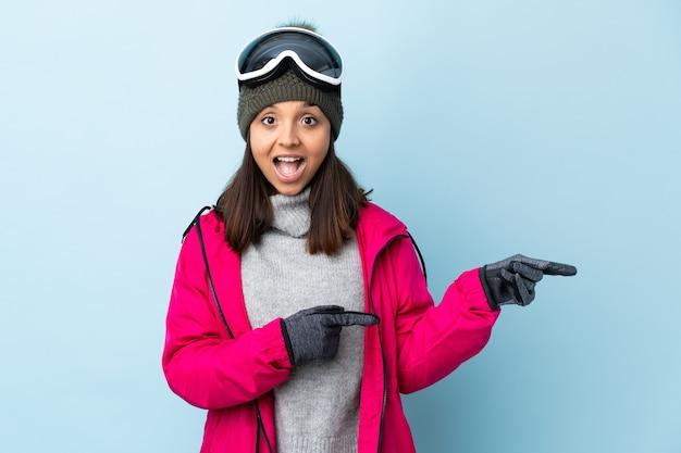 Het gemengde meisje van de rasskiër met snowboardglazen over geïsoleerde blauwe verraste en wijzende kant.