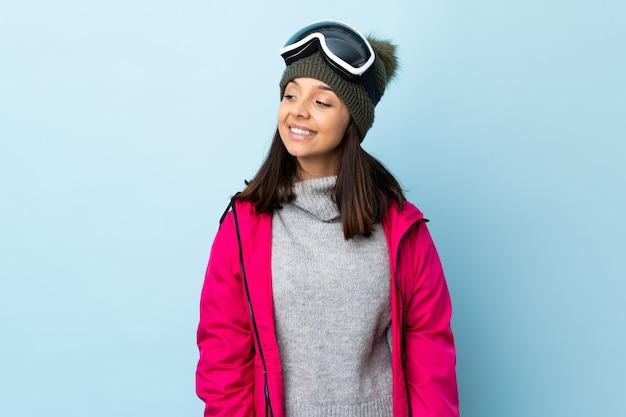 Het gemengde meisje van de rasskiër met snowboarding glazen over geïsoleerd aan de kant en blauw die glimlachen glimlachen