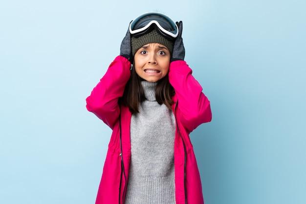 Het gemengde meisje van de rasskiër met snowboarding glazen over geïsoleerde blauwe muur die zenuwachtig gebaar doen