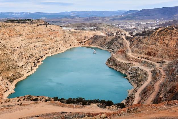 Het geopende blauwe hart van de aarde - verlaten steengroeve met een hartvormig meer op de bodem