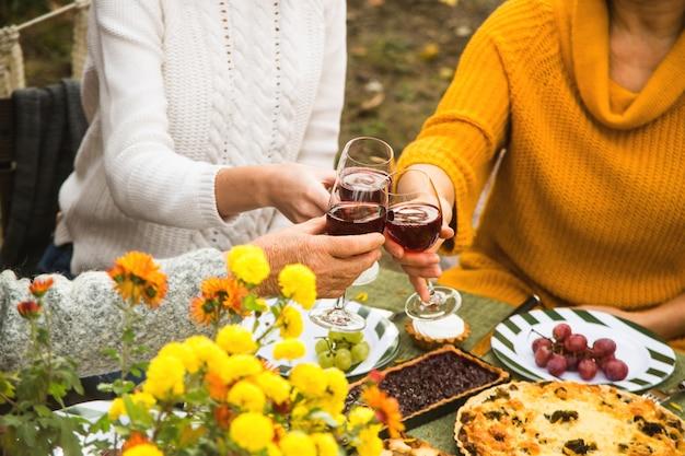 Het gerinkelglazen van vrouwen met wijn bij het diner van de de herfstfamilie.