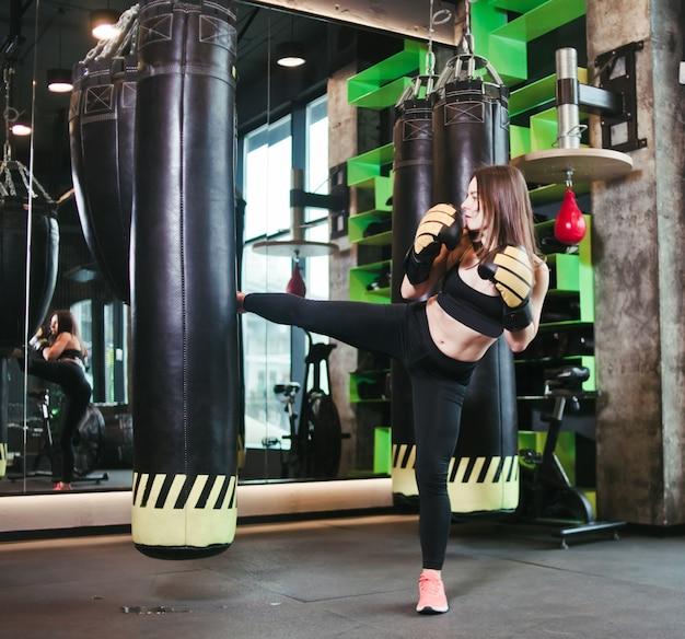 Het geschikte meisje in sportkleding en bokshandschoenentreinen schopt tegen bokszak bij donkere gymnastiek.
