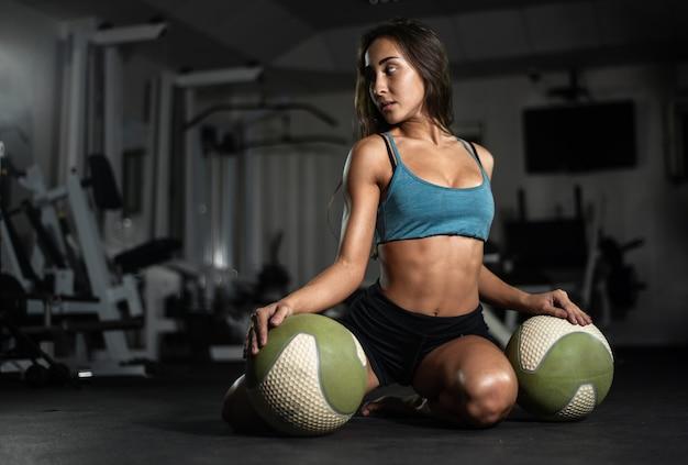 Het geschiktheidsmeisje stelt met ballen in de gymnastiek