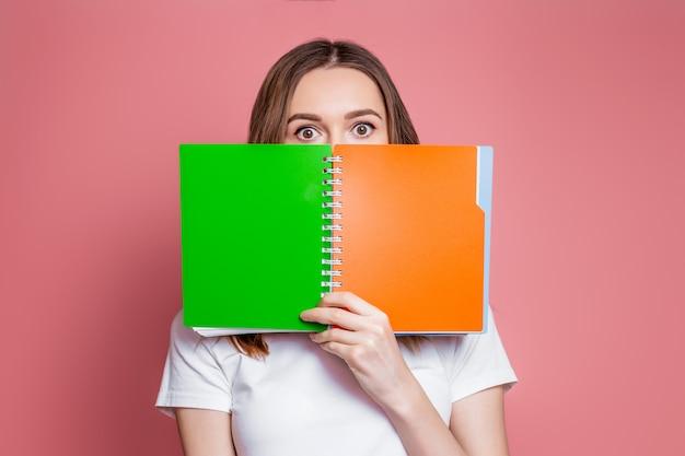 Het geschokte jonge meisje verbergt haar gezicht achter een notitieboekje dat over roze achtergrond wordt geïsoleerd