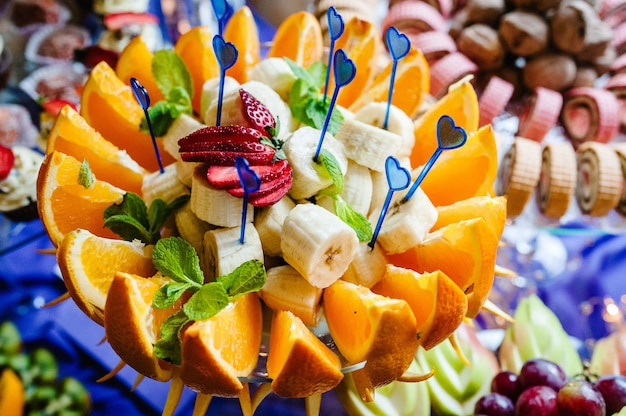 Het gesneden fruit op een bord. sinaasappel, banaan, aardbei, munt, druiven. in een glazen plaat, vaas. zoete tafel. toetje. de zoetheid. zachte toon. detailopname