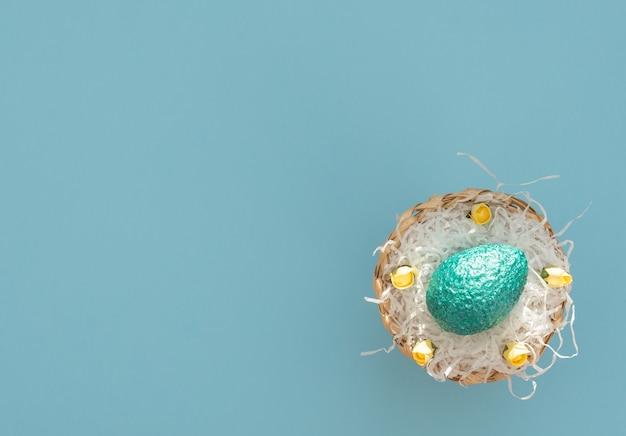 Het geverfde blauwe paasei ligt in een eiermand met wit papier als een nest en gele lentebloemen op blauw