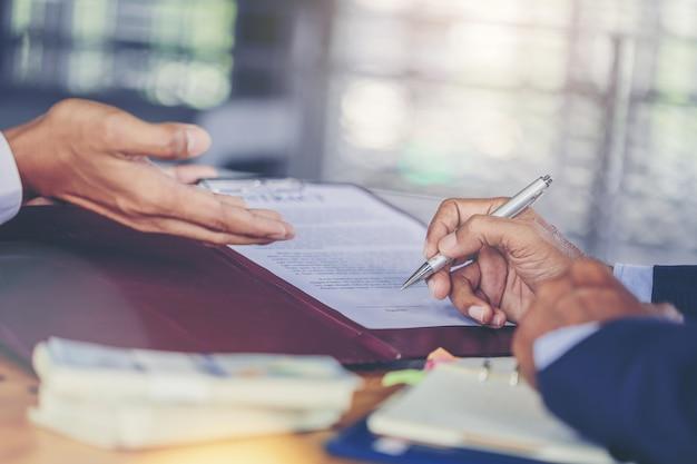 Het gewassenbeeld van zakenman zet handtekening op contract op commerciële vergadering en het overgaan van geld na onderhandelingen met bedrijfspartners