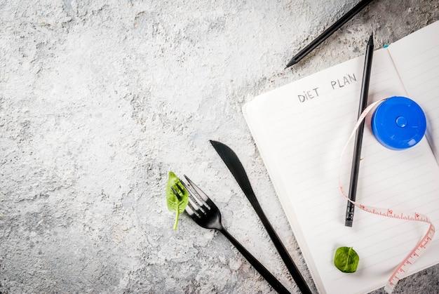 Het gewicht van het dieetplan verliest concept, verse groentesalade met vork, mes, blocnote, grijze het exemplaar ruimte hoogste mening van de steenlijst