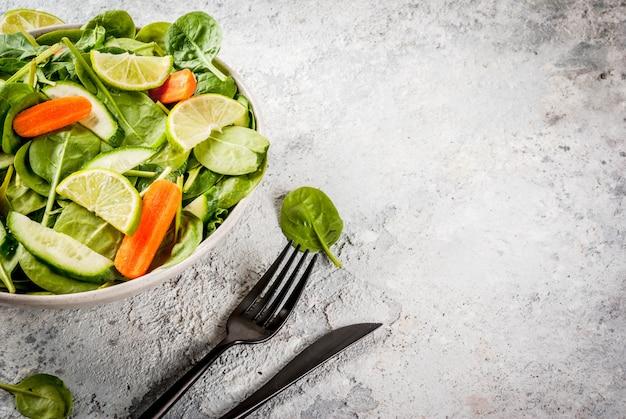 Het gewicht van het dieetplan verliest concept, verse groentesalade met vork, mes, grijze het exemplaarruimte van de steenlijst
