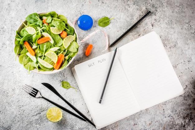 Het gewicht van het dieetplan verliest de salade van de concepten verse groente met van de de notepadgrey steen van het vorkmes de lijst