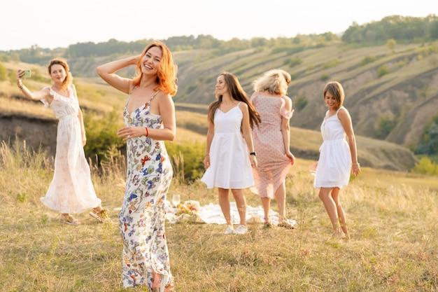 Het gezelschap van gelukkige vriendinnen die plezier hebben en buiten dansen op een picknick in de heuvels.