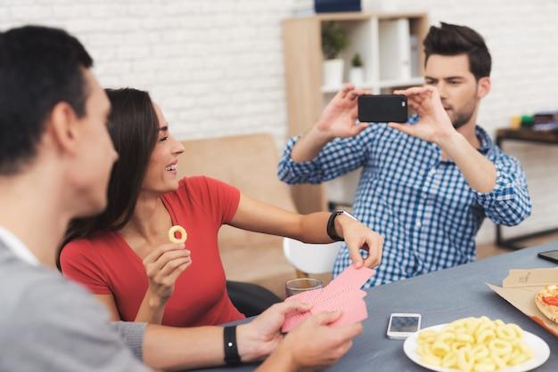 Het gezelschap van jongeren speelt kaarten