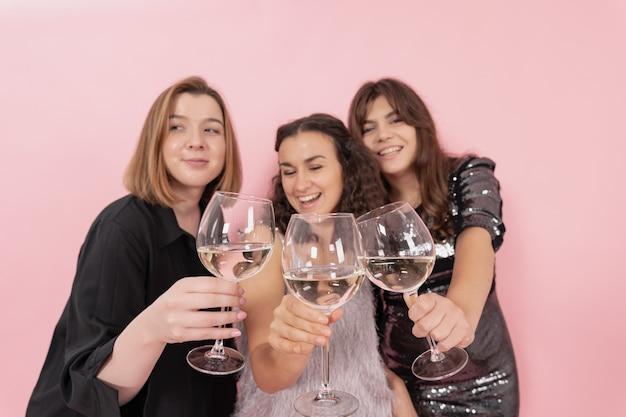 Het gezelschap van meisjes met glazen champagne op een roze achtergrond