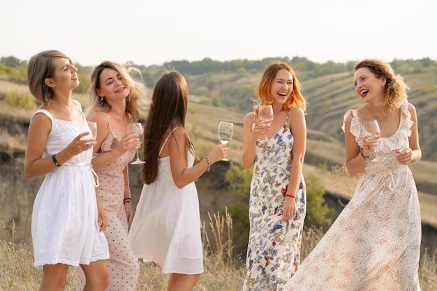 Het gezelschap van prachtige vrienden die plezier hebben en genieten van een zomerse groene picknick, dansen en alcohol drinken. mensen concept.