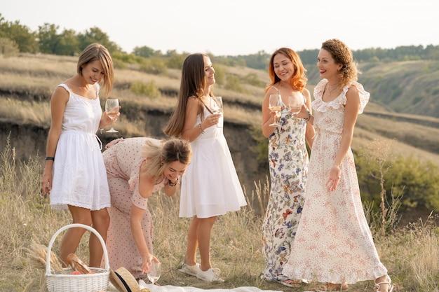 Het gezelschap van prachtige vriendinnen die plezier hebben en genieten van een zomerse groene picknick, dansen en alcohol drinken. mensen concept.