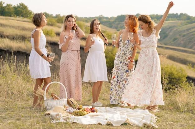Het gezelschap van prachtige vriendinnen die plezier hebben en genieten van een zomerse groene zomerpicknick, dansen en alcohol drinken. mensen concept.