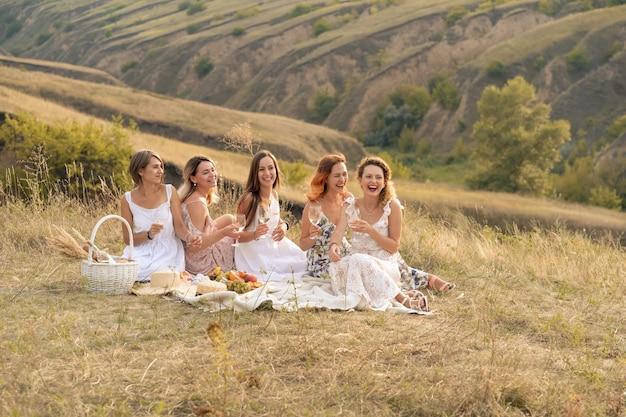 Het gezelschap van prachtige vriendinnen die plezier hebben, wijn drinken en genieten van een picknick in de heuvels