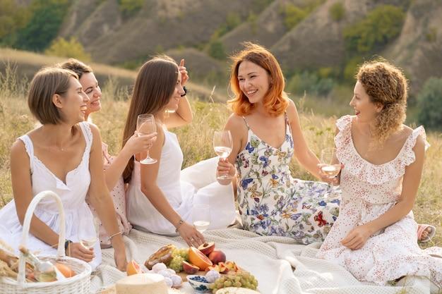 Het gezelschap van prachtige vriendinnen die plezier hebben, wijn drinken en genieten van picknick in het heuvellandschap