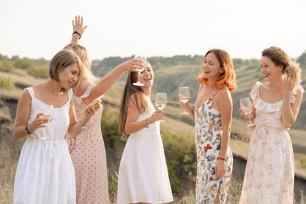 Het gezelschap van prachtige vrouwelijke vrienden die plezier hebben en genieten van een zomerse groene picknick, dans en alcohol drinken. mensen concept.