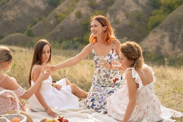 Het gezelschap van prachtige vrouwelijke vrienden die plezier hebben, wijn drinken en genieten van een picknick in het heuvellandschap
