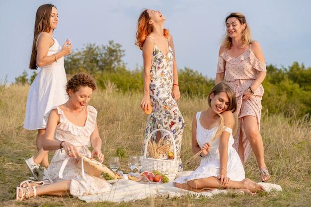 Het gezelschap van stijlvolle gelukkige vriendinnen plezier op outdoor picknick in retrostijl