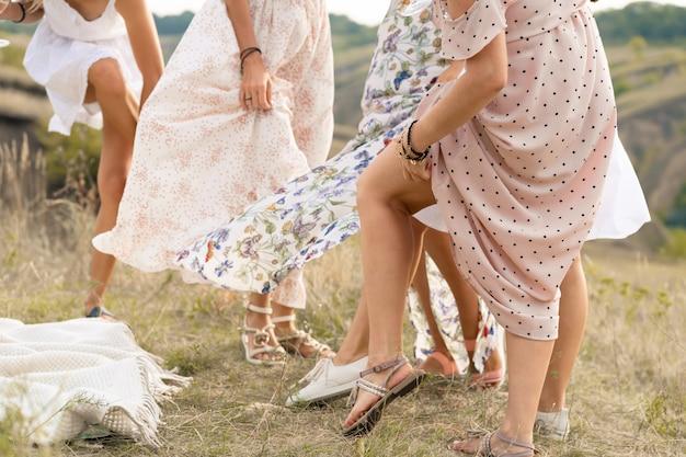 Het gezelschap van vriendinnen die lol hebben en dansen op het zomerveld in lange jurken met hun benen. zomer landelijke stijl picknick concept.