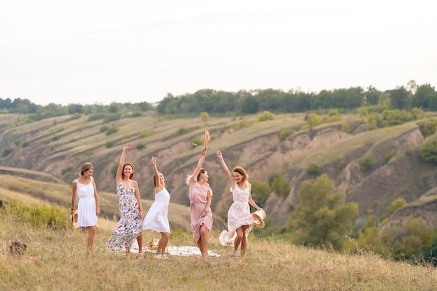 Het gezelschap van vrolijke vriendinnen beleeft een geweldige tijd samen op een picknick op een schilderachtige plek met uitzicht op de groene heuvels. meisjes in witte jurken dansen in het veld