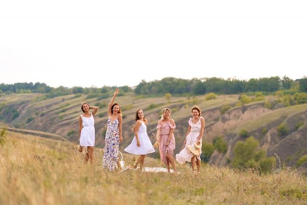 Het gezelschap van vrolijke vriendinnen heeft een geweldige tijd samen op een picknick op een schilderachtige plek met uitzicht op de groene heuvels. meisjes in witte jurken dansen in het veld